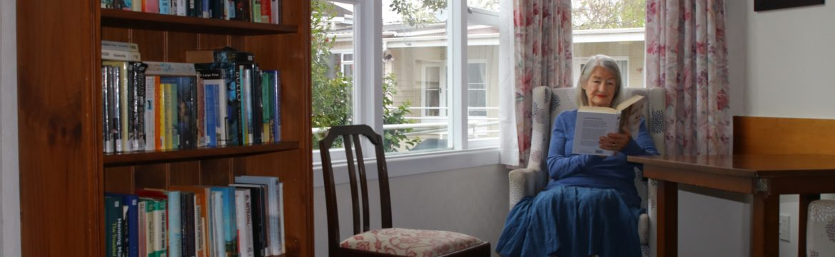 Sunrise Healthcare Ltd elderly woman sitting in a chair reading next to a window with a bookshelf in view.