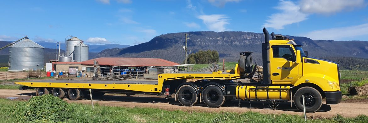 Brianna Tilt Trays & Towing Pty Ltd. yellow semi with towing trailer on a road with a mountain behind.