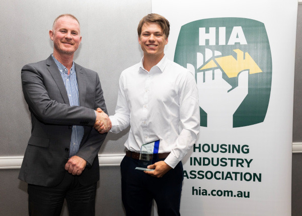 Housing Industry Association Ltd. HIA two men shaking hands with an HIA sign to the side.
