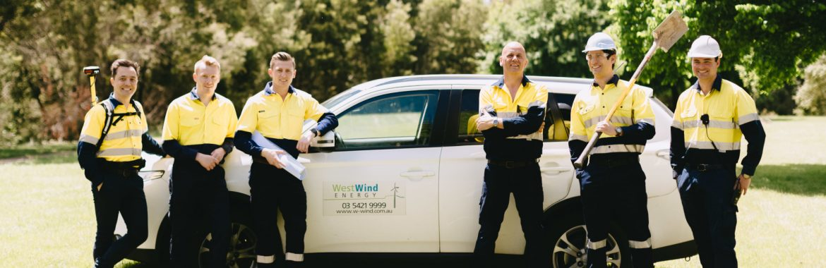 WestWind Energy employees posing for a group photo by a car with the WestWind logo.