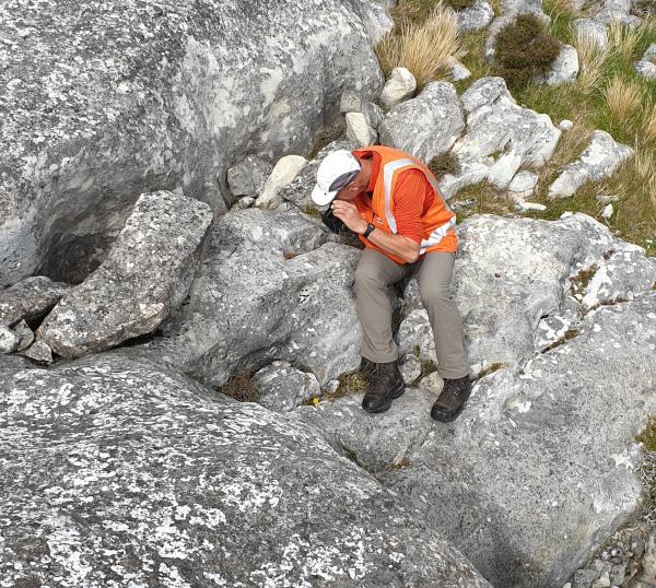 MainPower New Zealand Limited employee inspecting rocks.